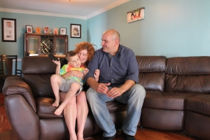 JACK FIRNENO / WIRE PHOTO Elizabeth and George Tolis sit in their home with their youngest son, Emmett. The Jamison couple of three children on the autism spectrum: 7-year-old twins Damian and Zack and 5-year-old Emmett.