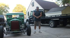 JACK FIRNENO /WIRE PHOTO Bernie Bernstein stands between his 1929 Model A Ford and International 4300 truck. He uses the latter to tow his vehicles to and from raceways and other events. Now, he's fighting for a zoning variance to keep the truck on his property.